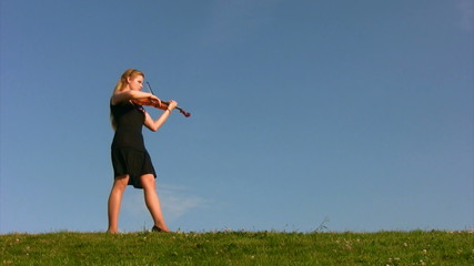 female musician walks on meadow and plays violin
