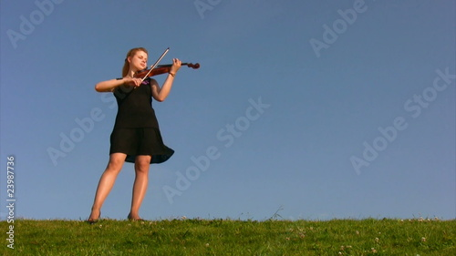 young woman stands on hill and plays violin