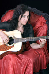 girl in red-black Spanish clothes plays a guitar