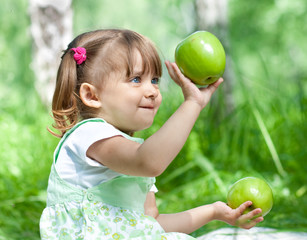 Little girl portrait with two green apples in her hands outdoor