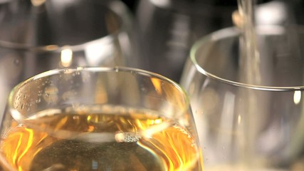 Macro video of white wine pouring into four glasses
