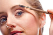 Woman applying make-up using eyebrow brush
