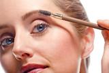 Woman applying make-up using eyebrow brush