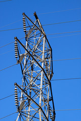 High tension power lines against a blue sky background