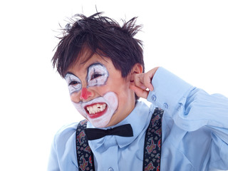 child clown covering his ear with his pointer finger