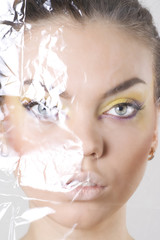 Female face wrapped in cellophane