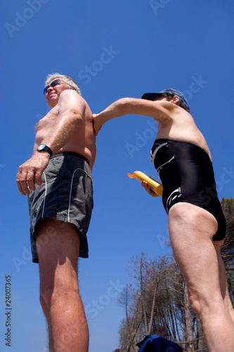 Mature woman applying suncream to mature man