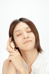 貝を耳にあてる女性