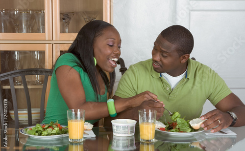 Young ethnic couple by table eating breakfast - 24013378