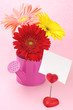 Colorful gerberas in watering can and note holder