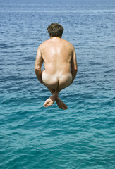 naked man jumping into the sea