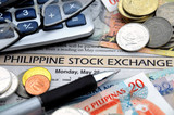 Philippine money on a newspaper stock exchange report poster
