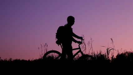 silhouettes of bicyclists with knapsacks against sky