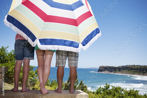 Friends under beach umbrella on patio overlooking ocean