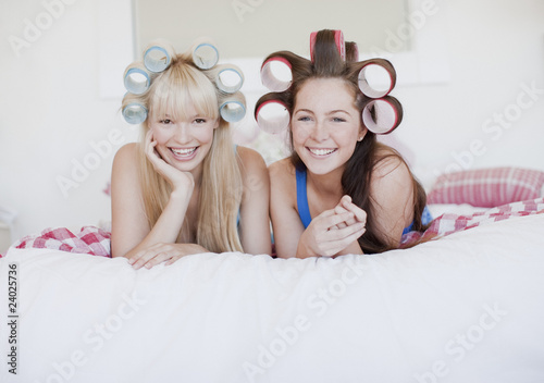 Women laying on bed with curlers in hair