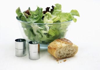 saladier de salade verte avec morceau de pain et sel et poivre