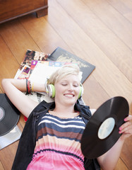 Woman laying on floor listening to headphones and holding music record