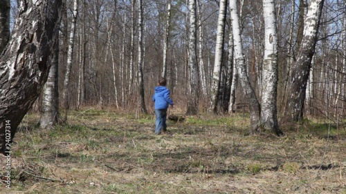 boy runs to spring brich grove from camera