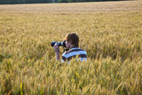 boy takes pictures in corn field
