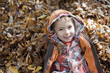 Boy laying in pile of autumn leaves
