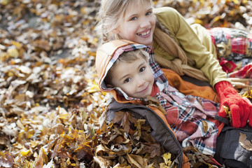 Children laying in pile of autumn leaves