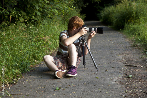 boy taking pictures with tripot of leafes in detail