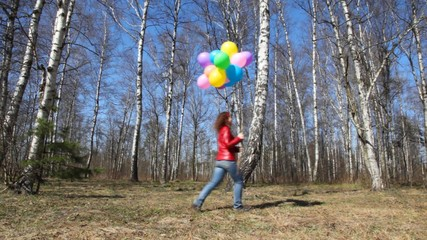woman with balloons walks in grove