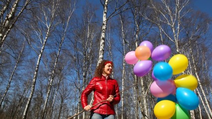 woman holds bunch of balloons in forest