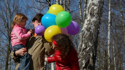 family with bunch of balloons in forest