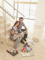 Couple reviewing carpet samples on stair in empty house
