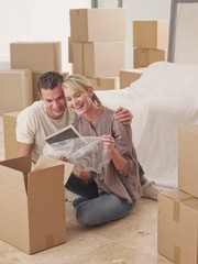 Couple looking at picture frame amidst moving boxes