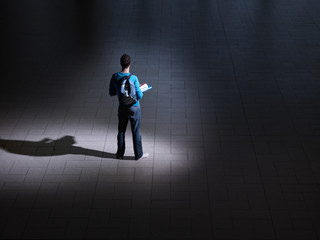 Male student with backpack and books in dark room