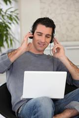 Homme écoutant de la musique sur ordinateur