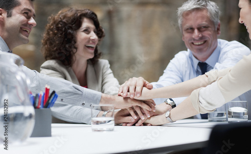 Business people stacking hands in meeting