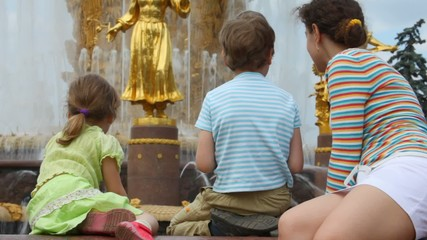 Mother, son and daughter sit near Fountain Friendship of Peoples
