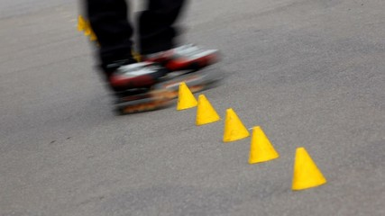 Experienced roller skater rides in park among yellow cones