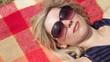 CU, PAN, Female with sunglasses sunbathing on blanket