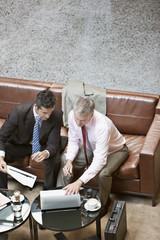 Businessmen using laptop in lobby