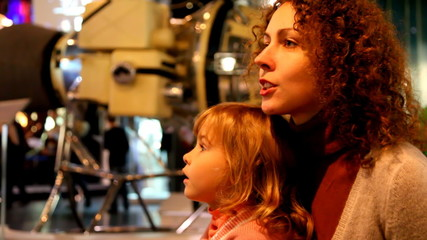 mother with daughter in space museum, space probe on backgrownd