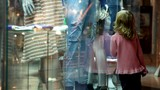 girl walking along museum display window with exhibits