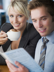 Businesswoman drinking latte and businessman reading menu