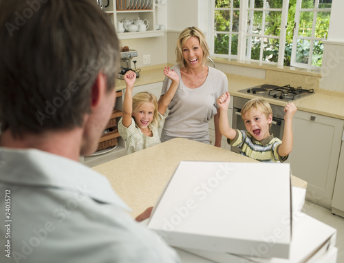 Man arriving in domestic kitchen with pizza boxes and family cheering