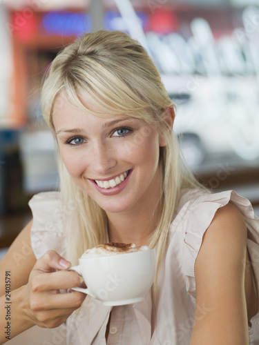 Woman drinking latte at cafe