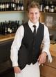 Waiter leaning on counter in restaurant