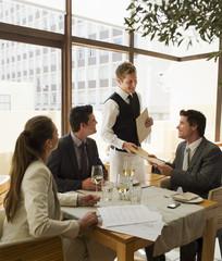 Waiter handing business people menus at restaurant table