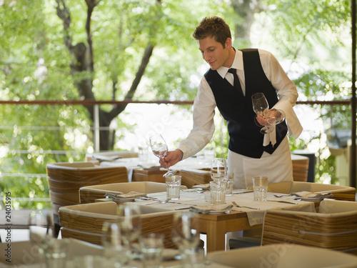 Waiter placing glasses on table in restaurant