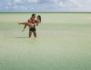 Man carrying woman and wading in ocean