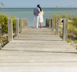 Couple on boardwalk hugging and looking at ocean