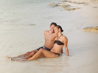 Couple sitting in ocean surf