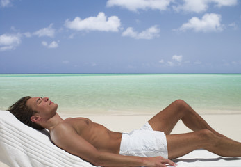Man on beach sunbathing on lounge chair with eyes closed
